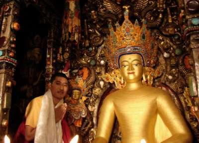 拉薩大昭寺,一名信徒與佛陀12歲等身像合影。(圖/ziyi xu@flickr)
