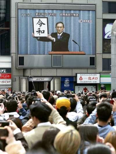 日本內閣官房長官菅義偉公布新年號「令和」,東京民眾也在街頭收看即時新聞,並且拿手機拍下這歷史性的瞬間。(美聯社)
