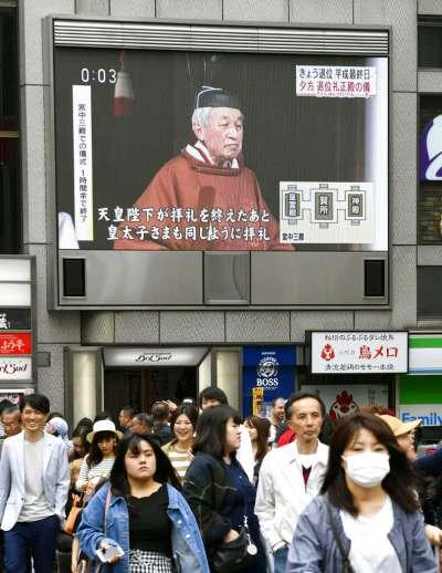 大阪街頭的大型螢幕30日上午報導明仁天皇退位的消息,不過明仁參加相關儀式的虔敬神情,與街上熙來攘往的日本人民形成有趣對比。(美聯社)