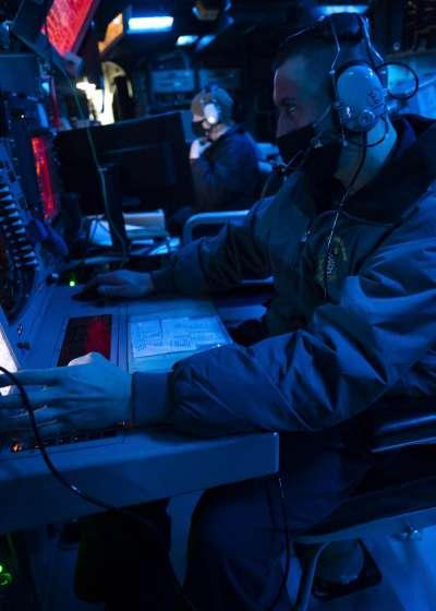 美軍驅逐艦「威爾伯號」(USS Curtis Wilbur)30日通過台灣海峽,一名軍官在艦上的戰鬥資訊中心監看周遭事態。(美國海軍官網)