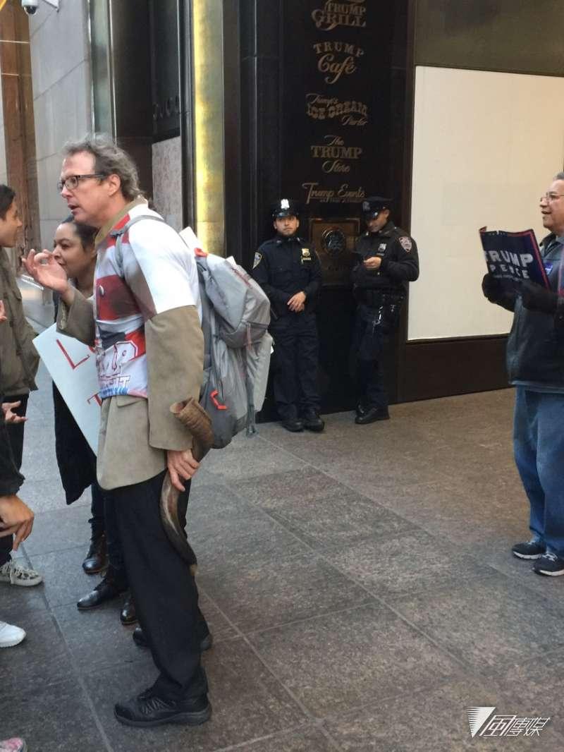 在川普大樓外舉牌支持川普的美國民眾。(簡恒宇攝)