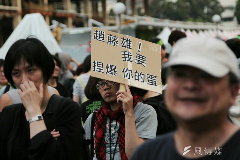 松菸護樹遊行中,一位帶著紅圍巾的民眾高舉「趙藤雄!我要捏爆你的蛋」,表達對遠雄的不滿。(余志偉攝)