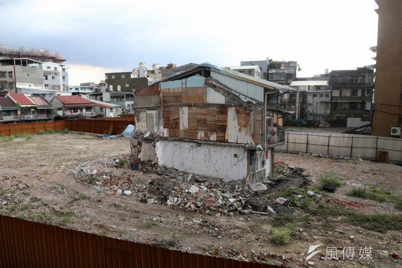走近台北市汀州路340巷旁的1處工地,透過一旁圍起的鐵皮圍欄,可以看到一幅奇異的景象─1棟增建至3樓的老房子,孤伶伶地站在一大片空地上。(吳逸驊攝)