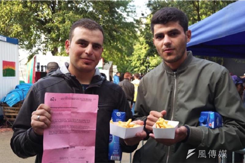 B(左)和M(右),手拿著申請庇護的通知書、薯條和蘋果汁。(作者提供)