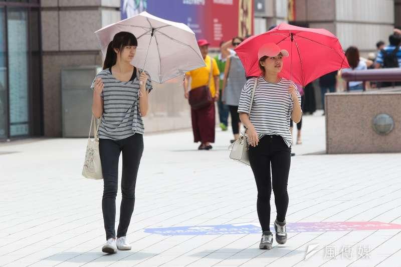 台北烈日高溫,今日用電量達到歷年7月第1高。圖為民眾紛紛撐起陽傘遮陽。(資料照,顏麟宇攝)