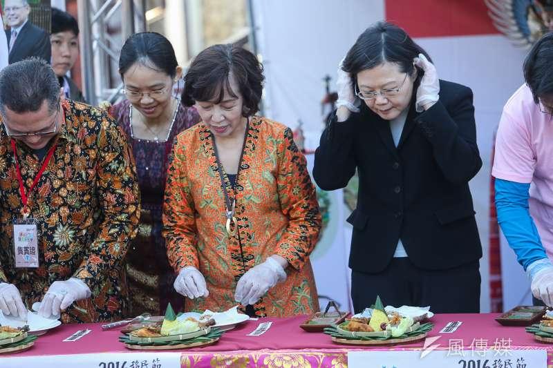 總統蔡英文(右)慶祝移民節,致詞表示台灣會繼續把門打開,包容多元文化,蔡英文在印尼攤位非常專注學習做雞絲糯米飯,雖戴了手套,卻習慣地挽了頭髮。(陳明仁攝)