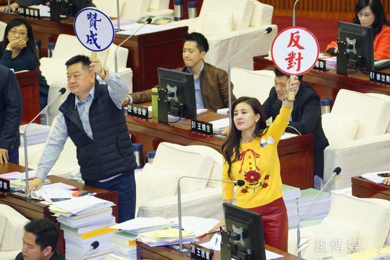 台北市議會進行總預算表決,議員王欣儀、王孝維分別舉牌引導同黨議員投票。(盧逸峰攝)