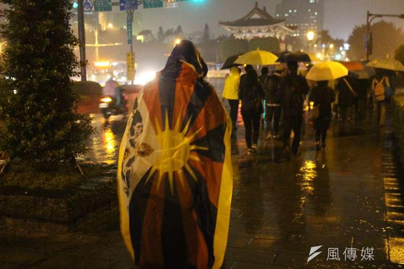 10日是西藏抗暴58周年,西藏台灣人權連線發起「310西藏抗暴 夜行一起挺圖博」活動,民眾披著代表西藏的「雪山獅子旗」於雨中夜行。(方炳超攝)