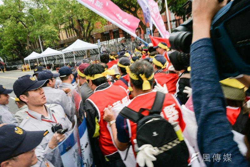 反年金改革團體抗議,民眾企圖以繩子拉倒柵欄,突破立法院的青島東路防線。(甘岱民攝)