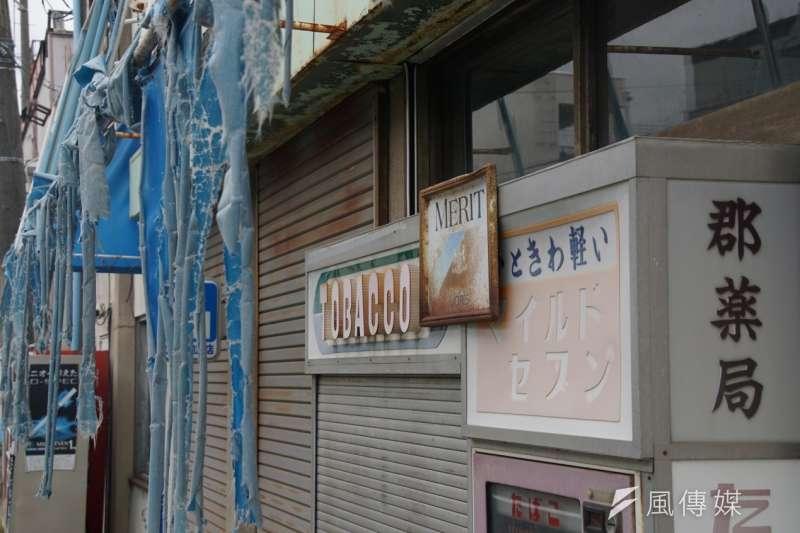 街坊招牌與自動販賣機,上頭滿是鏽斑。(盧逸峰攝)