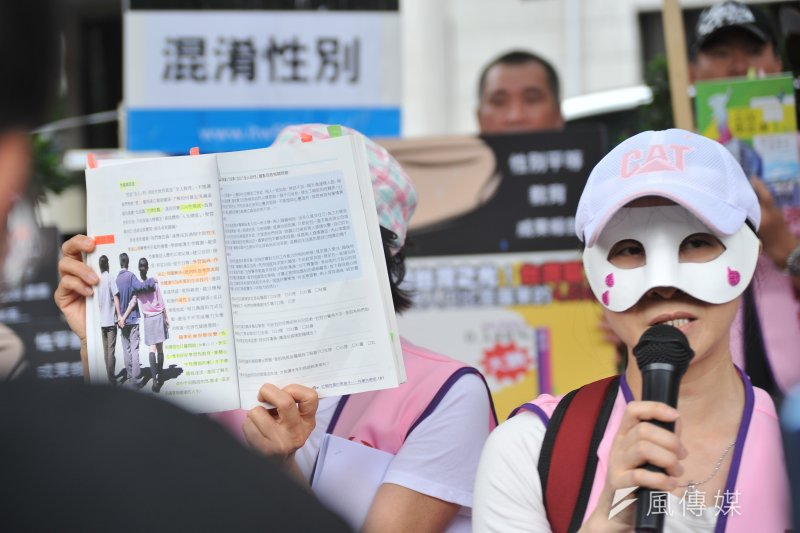 媽媽盟「媽媽最大的憂慮-不當性平教育退出校園」記者會,一位戴面具的家長,並指課本上一張3人並肩(兩男一女)的圖,是教導「多P」行為。(甘岱民攝)