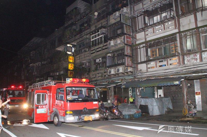 基隆市區華三街公寓大樓凌晨遭縱火,消防人員迅速把火撲滅。(圖/張毅攝)