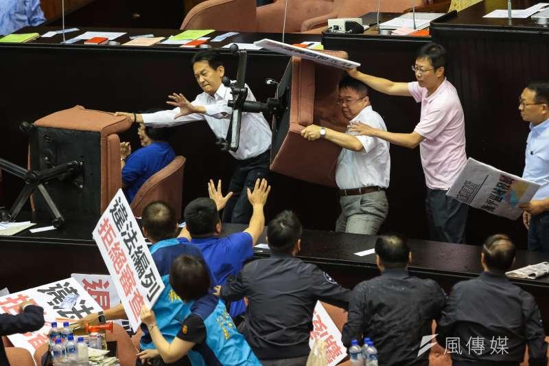 立法院14日進行前瞻計畫預算報告時,民進黨立委吳秉叡於主席台前扛起座椅,準備丟向國民黨委員。(顏麟宇攝)