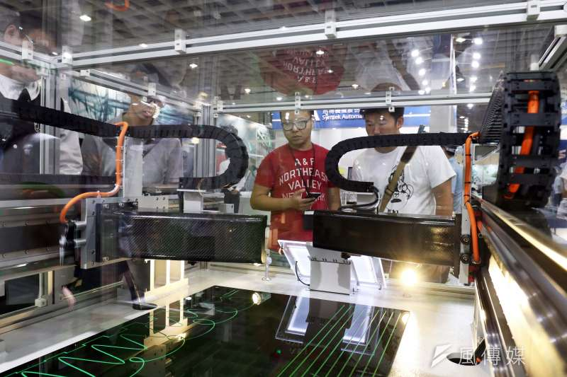 圖為「台灣機器人與智慧自動化展」中參觀者仔細端詳展出機器運作。(蘇仲泓攝)