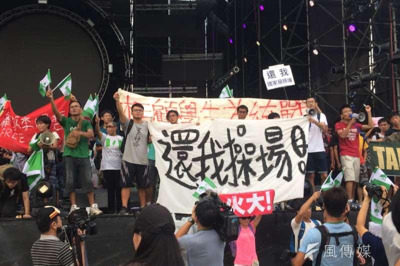 「中國新聲音」歌唱選拔會24日於台大操場舉辦,抗議學生、社運團體佔領舞台高舉標語。(謝孟穎攝)