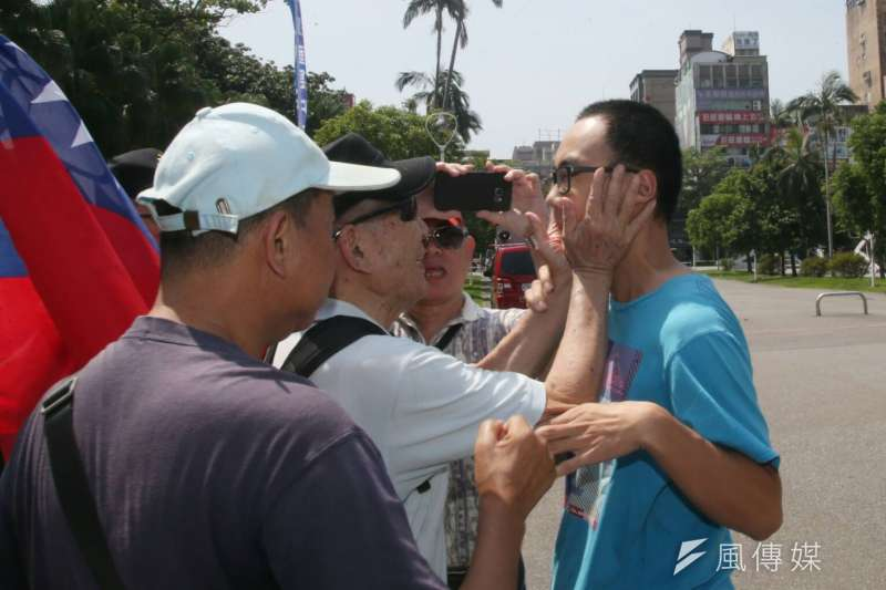 藍天行動聯盟26日在台大校門口抗議「台獨入侵校園」,一名台大學生路過,卻遭藍天盟拍臉頰。(陳明仁攝)