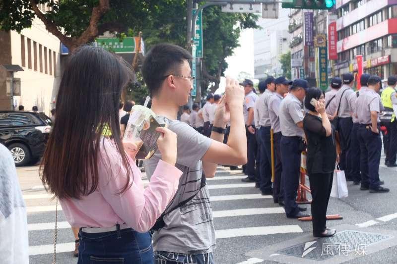 台灣人對李明哲的「漠然」,讓作者感到失落。台灣擁有巨大的自由,卻陷在藍綠先行的對立情緒中。圖為統促黨遊行,旁觀的中國旅客。(謝孟穎攝)