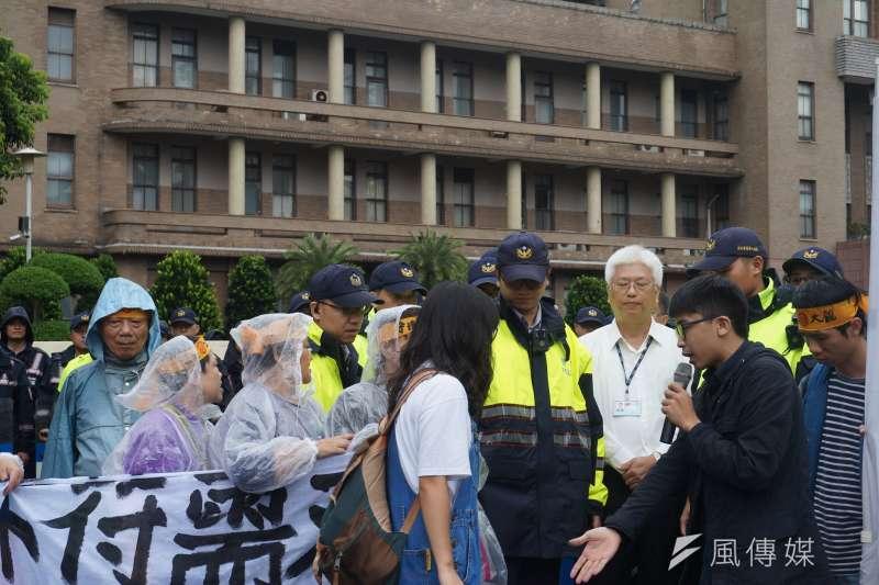 政院代表張洪鈞出現於記者會,但不願站在居民與媒體面前,躲在大批警力周圍。(陳子萱攝)