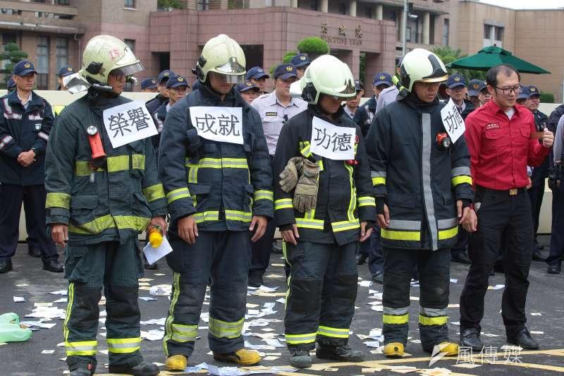 20171024-消防員工作權益促進會24日於政院門口召開「蜂蛇回歸開倒車,基層做死誰人知?」記者會,並於消防同仁身上貼上「榮譽、成就、功德」的標語。(顏麟宇攝)