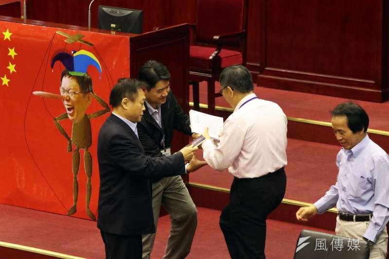 台北市議會13日下午進行市政總質詢,圖為民進黨議員王世堅質詢時,將柯文哲的三本著作還給他,要柯好好回去反省。(蘇仲泓攝)