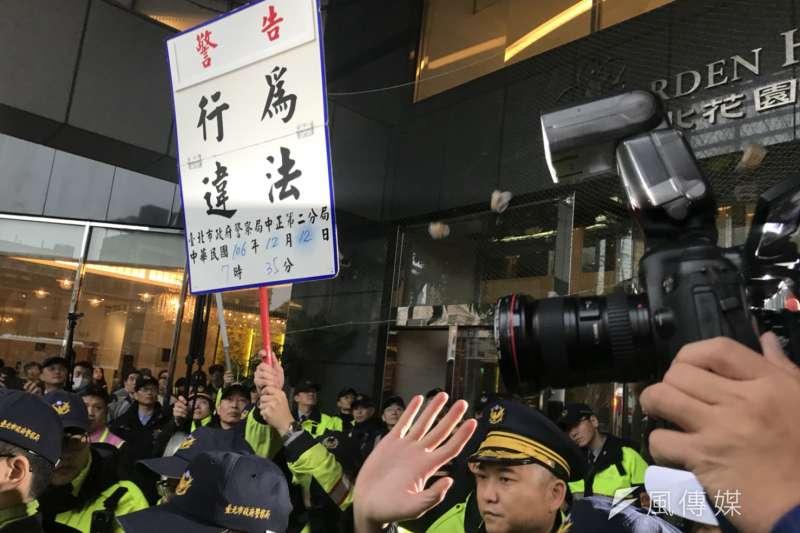 20171212-行政院長賴清德與工商團體12日於台北市五星級飯店花園酒店進行早餐會,勞工團體在外集結為《勞基法》修法抗議。圖為警方對勞團舉牌「行為違法」。(謝孟穎攝)
