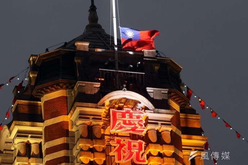 107年元旦總統府升旗音樂會塔樓上的憲兵升旗時,用力將國旗展開,新的一年揭開序幕。(蘇仲泓攝)