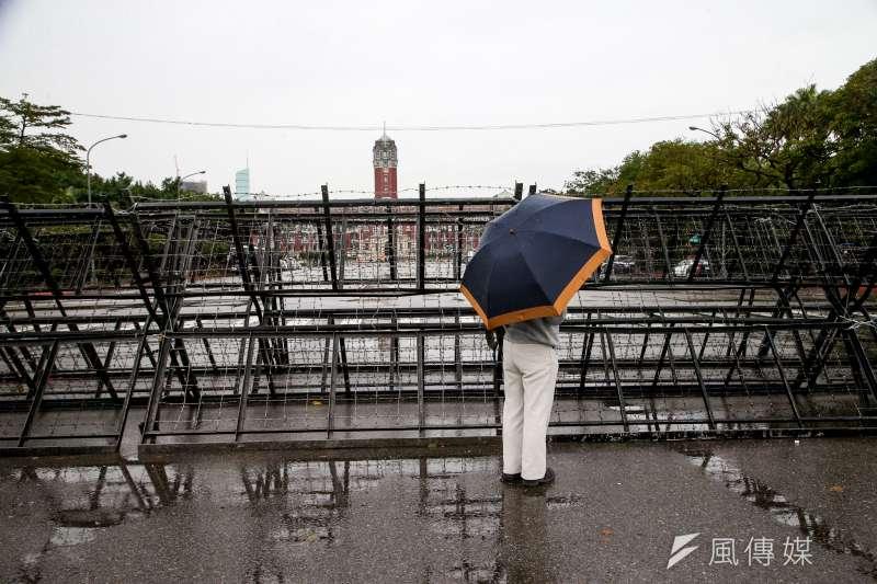 寒雨中被拒馬圍堵住的總統府,成了遊客拍照的景點。(陳明仁攝)