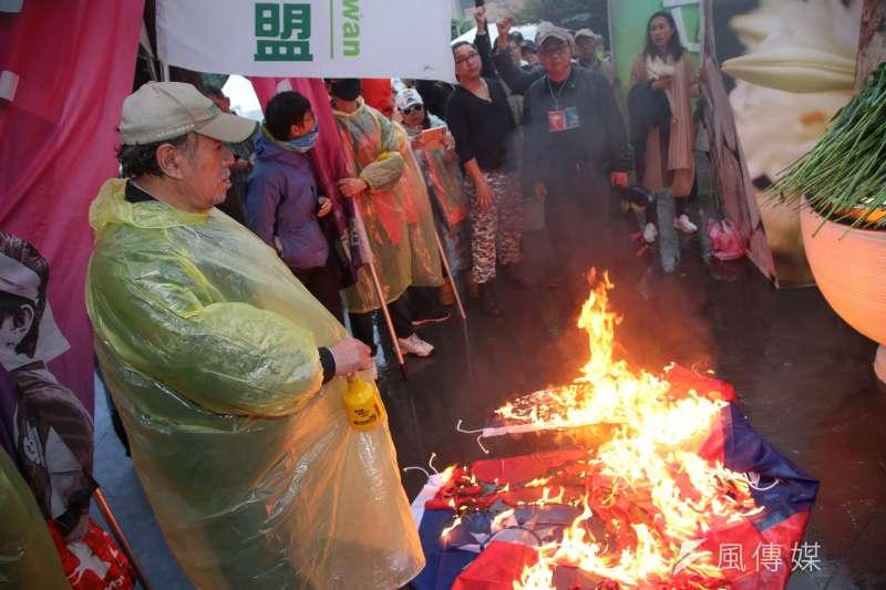 作者認為,執政黨倡導「轉型正義」之際,卻出現嚴以對人,寬以待己的兩面手法。圖為自由台灣黨主席蔡丁貴28日於「二二八事件71週年中樞紀念儀式」後,於紀念碑前焚燒國旗。(資料照,顏麟宇攝)