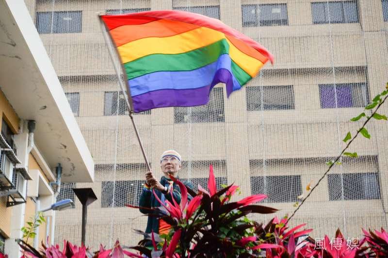 婚姻定義公投聽證會,祁家威在場外揮舞彩虹旗。(甘岱民攝)