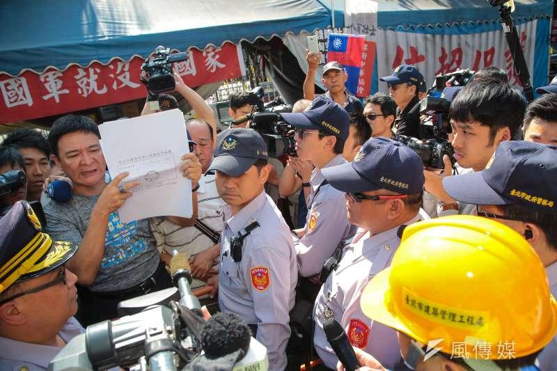 20180329-八百壯士成員羅叡達29日於八百壯士帳篷前,將申請資料給台北市建管處官員確認。(顏麟宇攝)