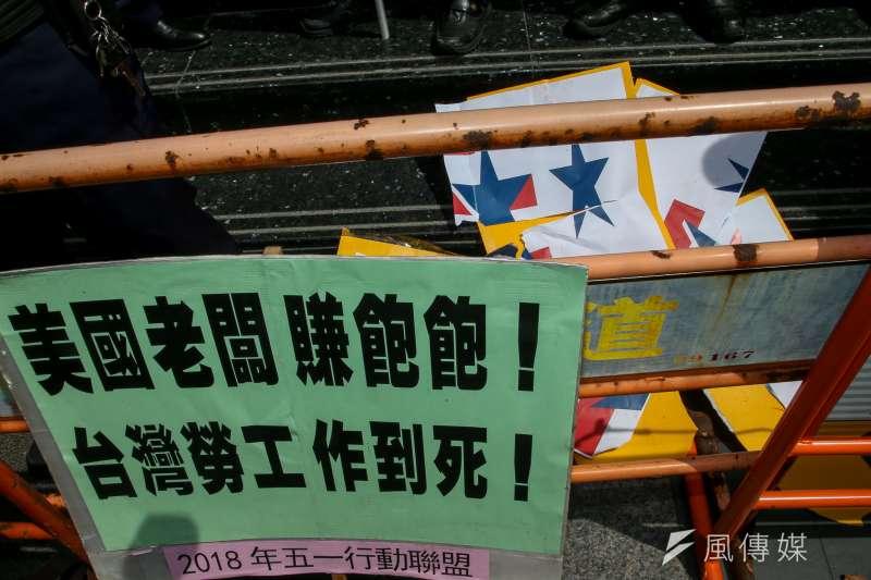 20180418-五一行動聯盟在遊行前夕,到台北美國商會抗議,抨擊美在台資本家是「台灣勞工作到死」的背後推力,把台北美國商會LOGO踩踏撕毀表達憤怒 。(陳明仁攝)
