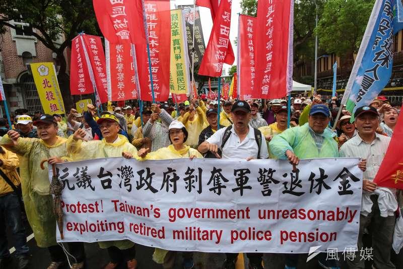 退休警消人員4月24日舉行警消不服從遊行,手持「抗議台灣政府剝奪軍警退休金」布條。(資料照,顏麟宇攝)