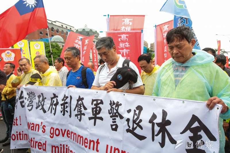 請注意!政府提撥的65%其實還是我們的錢!圖為退休警消人員手持「抗議台灣政府剝奪軍警退休金」布條,為國道公殉職員警默哀。(資料照,顏麟宇攝)