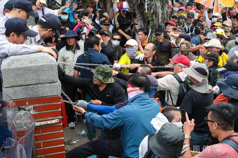 作者認為,退休軍公教手上沒有任何權力,無能為台灣現狀負責;退休軍公教也不是台灣社會的最大「受益者」。圖為反年改團體25日試圖衝入立院,以鐵鍊拉扯立院外圍牆欄杆。(顏麟宇攝)