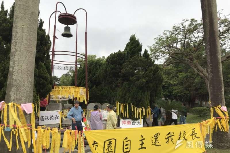 台大師生在傅鐘前綁黃絲帶抗議,繫布條「校園自主還我校長」,力挺大學自主。(吳尚軒攝)