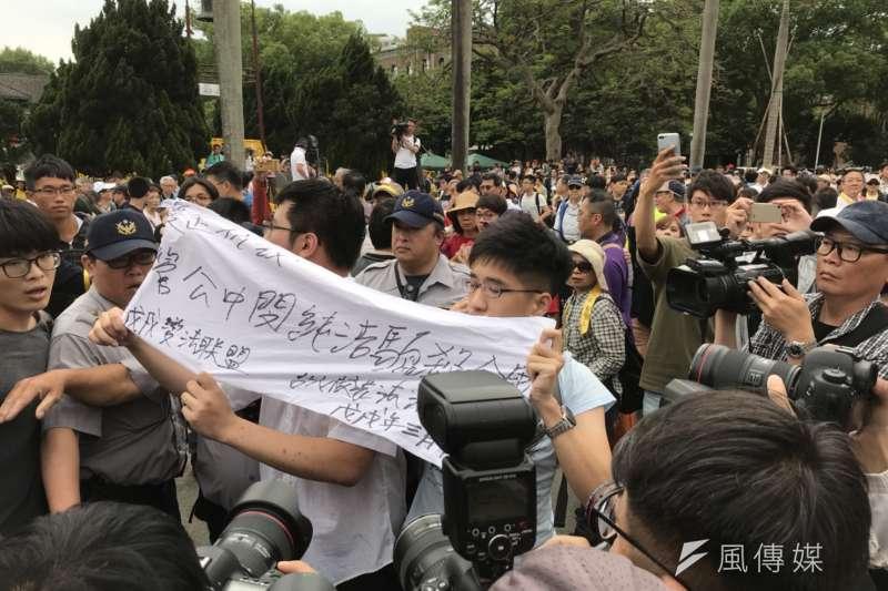 數名台大學生高舉「管中閔純潔騙殺全國」的布條於傅鐘另一頭經過,雙方並一度爆發衝突。(吳尚軒攝)