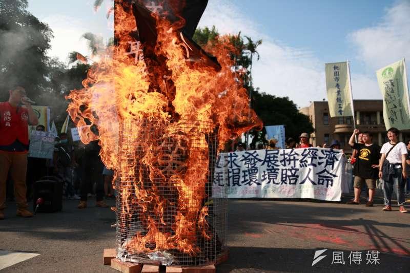 20180603-消防員工作權益促進會、台灣移工聯盟等多個團體3日發起「只求發展拚經濟,耗損環境賠人命」敬鵬大火聯合遊行。遊行團體於行政院前焚燒訴求布條。(簡必丞攝)