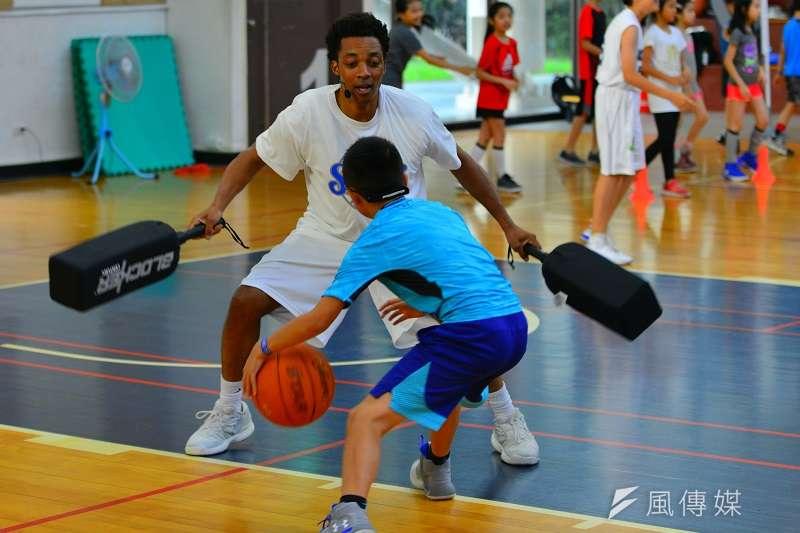 SBC 籃球體驗營客座教練布蘭登指導小朋友的動作。 (圖/金茂勛攝)