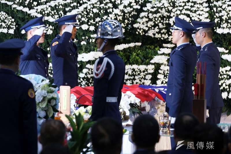空軍第五聯隊飛官吳彥霆喪禮,家屬在空軍樂隊演奏哀樂引領下,緩步從會場內走出,穿過由空軍儀隊列隊致敬的走道。(蘇仲泓攝)