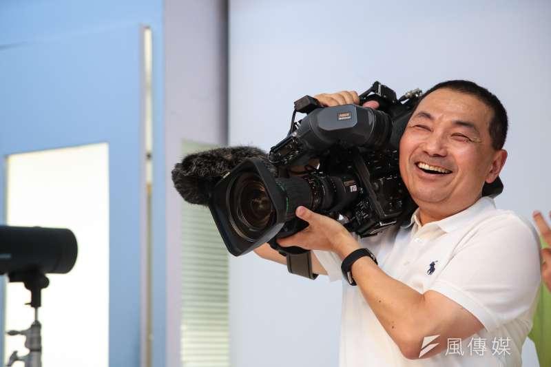 20180627-國民黨新北市長參選人侯友宜27日拍攝定裝照,並於現場扛起電視台攝影的攝影機。(顏麟宇攝)