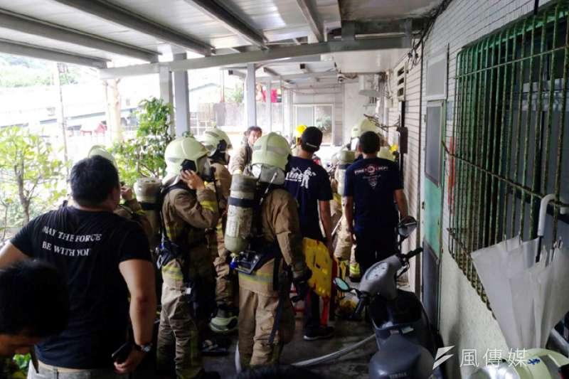 大批消防隊員破門進入民宅搶救出一名男子。(張毅攝)