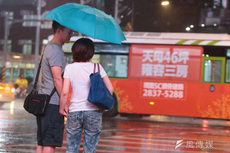 20180710-颱風瑪莉亞來襲,晚間風雨愈漸加驟,撐傘等待過馬路的情侶與行駛過的公車房地產看板形成有趣畫面。(顏麟宇攝)