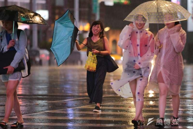 中颱瑪莉亞來襲,晚間風雨愈漸加驟,過馬路的民眾傘被吹到開花。(顏麟宇攝)