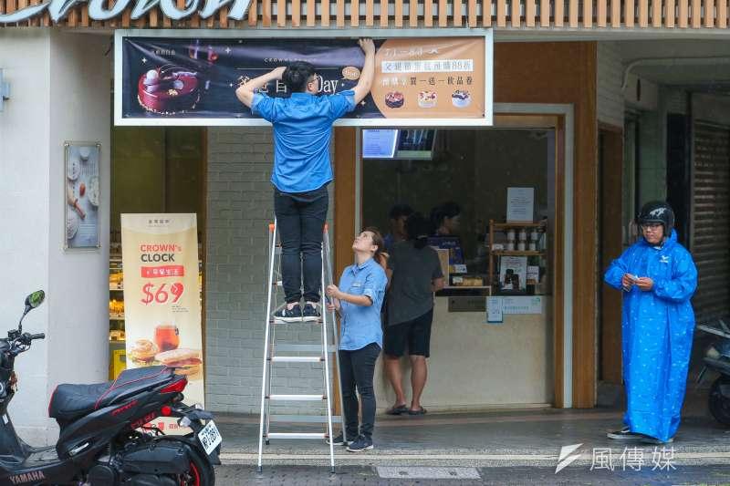颱風「瑪莉亞」飛掠北台灣,颱風假放不放又成爭論話題。風雨過後,店家掛回廣告招牌營業。(陳明仁攝)