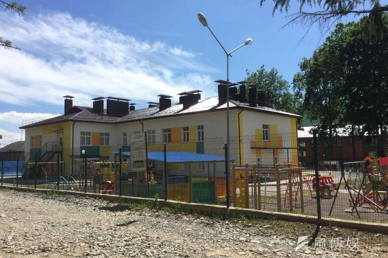 南奧塞梯亞列寧哥里鎮上的石子路,旁邊是類似學校和遊戲場的建築(簡恒宇攝)