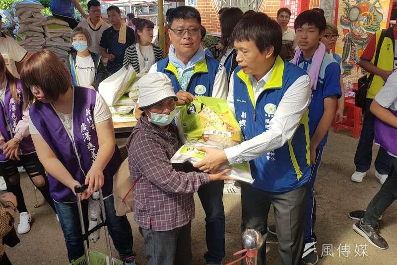 竹市不動產仲介公會理事長黃兆堂(中)帶領40位公會成員,協助發放捐助清寒愛心白米。(圖/方詠騰攝)