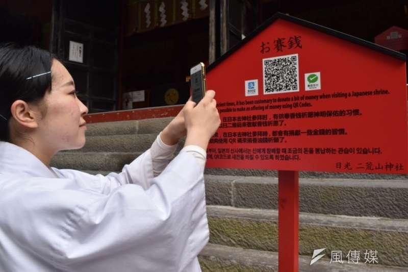 透過智慧型手機掃描看板上的QR條碼後,便可透過電子支付捐香油錢(圖/潮日本)