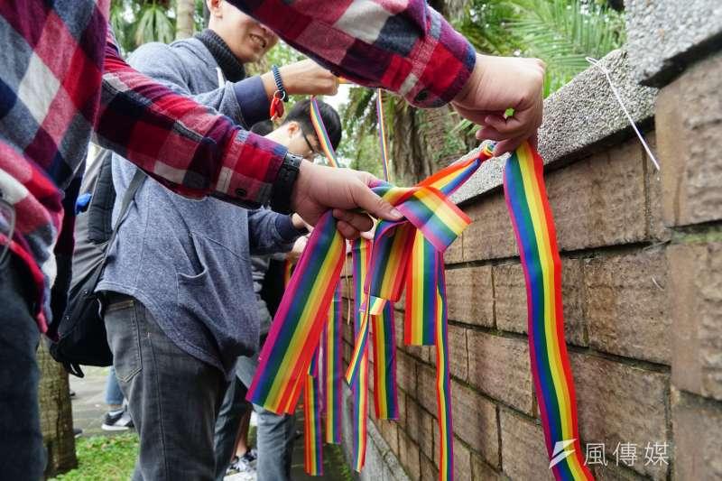 20181225-台大學生會「聖誕不快樂:彩虹上門暨台大校門彩虹旗行動」記者會,並在台大圍牆掛上彩虹旗與彩虹絲帶。(蔡親傑攝)