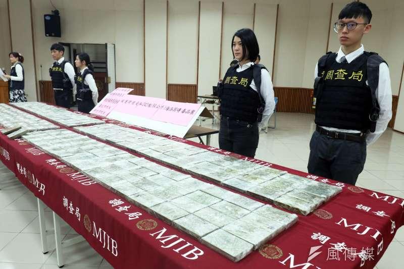 20190201-調查局台北市調查處下午召開記者會,說明本周在基隆港貨櫃查獲242塊海洛因磚一案。後方為現場戒護的武裝調查官。(蘇仲泓攝)