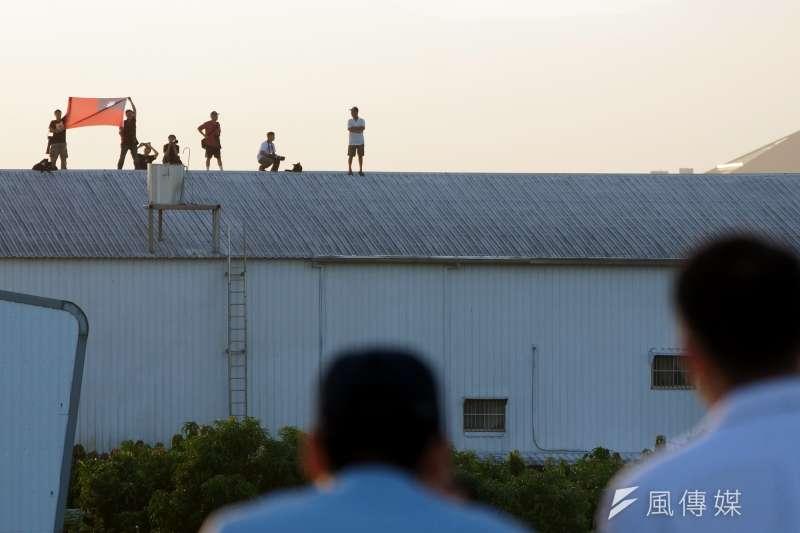 2014年9月,空軍在嘉義民雄戰備道演練,遠處軍事迷爬上4、5層樓高的鐵皮屋頂,張開國旗,展現對軍方的支持。(資料照,蘇仲泓攝)